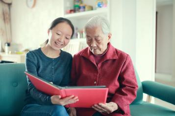 Two women reading together in a care home